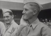 A young soldier strokes his meager scruff while another laughs at his beardless condition.
