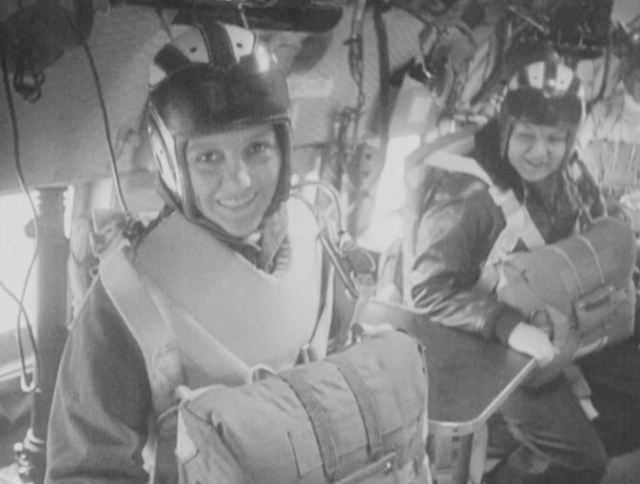 Women sailors prepare for a parachute jump at the end of their parachute rigger training.
