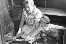 Mrs. John Holopainen and her grandson David start a fire in the Finnish bath-house on their farm. Forsythe. September, 1949 (16-G-168-1-N-10980)