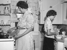 St. Francis Kansas, Mother Wilkins fries chicken and the youngest daughter, Marie, helps get dinner ready. Marie Wilkins is slicing cucumber for the salad. 7/21/44 Cooper (16-G-176-1-AAA-9435)