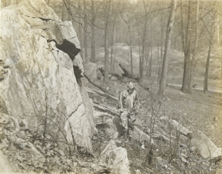 Women's Camouflage Reserve Corps study anti-detection methods, camouflaged against the rocks at Van Cortlandt Park, New York. Local ID: 165-WW-599G-21.