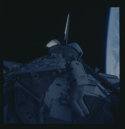 Photographic documentation of astronauts Kathryn D. Sullivan (red stripes) working on the Payload Bay during Extravehicular Activity (EVA). 255-STS-41G-48-040