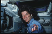 Mission Specialist (MS) Ride poses on aft flight deck while operating onorbit station controls. Overhead window W8 appears above Ride and remote manipulator system (RMS) translation hand control (THC) on her left.