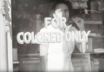 "A woman stands in the window of a segregated restaurant. Still from outtakes from ""Dixie, U.S.A"""