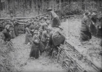 Women traverse a trench.
