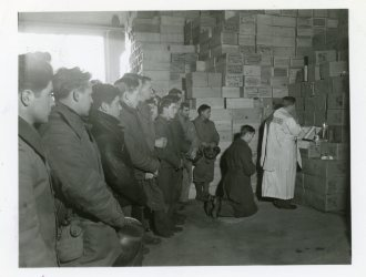 """111-SC-198774 """"A ration warehouse, on the docks in Antwerp, Belgium, served as a chapel for Christmas Day services, conducted by the port chaplain, Martin S. Durkin. The men left their work only long enough to attend Mass. A pile of ration crates served as an altar."""" Photo taken 12/25/1944"""