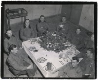 """111-SC-200483 """"Officers of the 101st Airborne Division have Christmas dinner in Bastogne, Belgium, while the city is still under German siege. Brigadier General Anthony C. McAuliffe (fourth on the left) commanded the division during the siege."""" Photo taken 12/25/1944"""