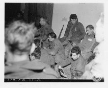 """111-SC-200856 """"While enemy shells scream overhead, outside, Christmas carols are sung by members of the 101st Airborne Division, under siege in Bastogne, Belgium, during 1944 midnight Christmas service. Shortly after this photo was taken, enemy bombers broke up the service."""" Photo taken 12/24/1944"""