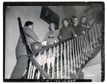 """111-SC-323599 """"The Sonvaux family greets Cpl. Wally J. Branson on the staircase as he arrives at their home to spend Christmas Eve. Namur, Belgium."""" Photo taken 12/24/1944"""