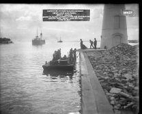 """Image shows workmen standing on a flat boat of some kind next to a pier on which the bottom of a lighthouse structure is seen. Two men in bowler hats stand on the pier while a worker in the background carries a sack over his shoulder. Two ships are seen in the distant background. Label on the original photograph reads, """"Improving St. Marys River, Michigan. New lock and canal. West Canal. Diver placing canvas cover and sandbag toe around new West Center Pier. June 12, 1911."""
