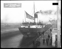 """Image shows Great Lakes bulk carrier ship """"Richard Trimble"""" making the first down lockage in the new lock. Label on original photograph reads, """"Improving St. Marys River, Michigan. New lock and canal, Farrell and Trimble in 3rd lock making first down lockage, October 21, 1914."""""""