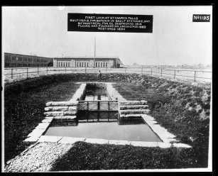 """Image shows a fenced off area around an old lock, about the size of a private swimming pool. Label on the photograph reads, """"First Lock at St. Marys Falls. Built 1797-8, for bateaux in Sault Ste. Marie, Ontario by Montreal Fur Co. Destroyed 1814. Floors and foundation uncovered 1889, restored 1890."""""""