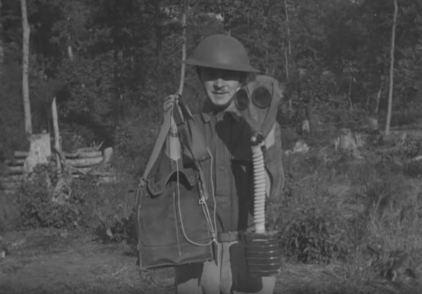 A soldier holds up his gas mask at the conclusion of The Manufacture of Gas Masks.