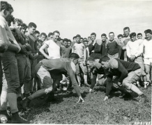 Original Caption: Football training has begun at constabulary headquarters at Bamberg, Germany. Practicing blocking are, Left to Right, Pfc, Bernard Clark of Sleepeye, Minn., and Pfc. Dang Davison of Downer's Grove, Ill. Coach Sandy Clark, wearing a white shirt, looks on from the rear left. August 20, 1946. Local ID: 111-SC-253147