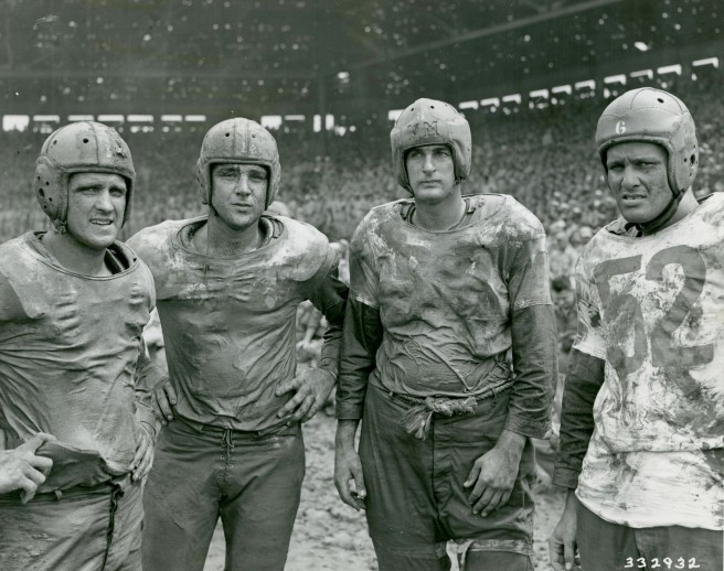 Original Caption: Four of Navy's mudstained stars pose after the Army and Navy football game on the Fourth of July at Rizal Stadium, Manila, P.I. Left to Right: Geyer, Bloomfield, New Jersey; Hall, Chicago, Illinois; Horjes, Tacoma, Washington; Youngberg, Woodstock, Illinois. July 4, 1945. Local ID: 111-SC-332932