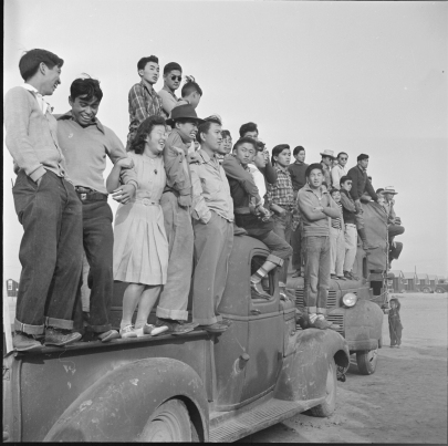 Original Caption: Rohwer Relocation Center, McGehee, Arkansas. Part of a crowd of evacuees watching a football game between the Stockton and Santa Anita teams. Local ID: 210-G-E299