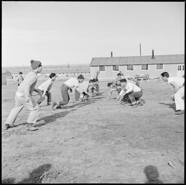 Original Caption: Granada Relocation Center, Amache, Colorado. Young center Niseis are football enthusiasts. Here during lunch hour, employees in administrative offices choose up sides and have a rousing half hour of touch. Local ID: 210-G-E541