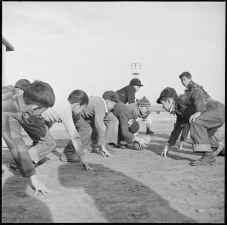 Original Caption: Granada Relocation Center, Amache, Colorado. Grade school boys playing touch football during the recess play period. Local ID: 210-G-E549