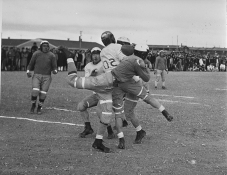 "Original Caption: Heart Mountain Relocation Center, Heart Mountain, Wyoming. An exciting bit of aciton between the ""All Stars"" and ""Jack Rabbits"" football teams, during a game at the Heart Mountain Relocation Center. At the moment it is difficult to say who has the ball. Local ID: 210-G-G211"