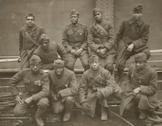 """Decorated soldiers of the 369th return home with their French Croix de Guerre awards. Front Row: Private Ed """"Eagle Eye"""" Williams, Corporal Herbert """"Lamp Light"""" Taylor, Private Leon Fraitor, Private Ralph """"Kid Hawk"""" Hawkins. Back Row: Sergeant H.D. Prinas, Sergeant Dan Storms, Private Joe """"Kid Woney"""" Williams, Private Alfred """"Kid Buck"""" Hanley, and Corporal T.W. Taylor. Local Identifier, 165-WW-127-8."""