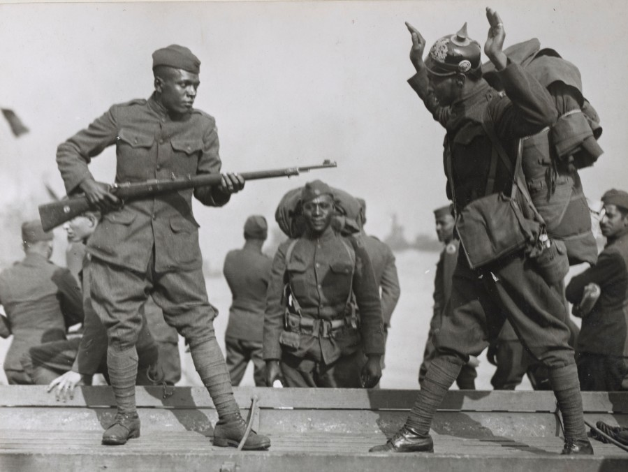 """Two members of the 505th Engineers show how they """"did it over there"""" during their return on the S.S. Roma.  Note the Imperial German helmet taken as a trophy.  Local Identifier, 165-WW-127-40."""