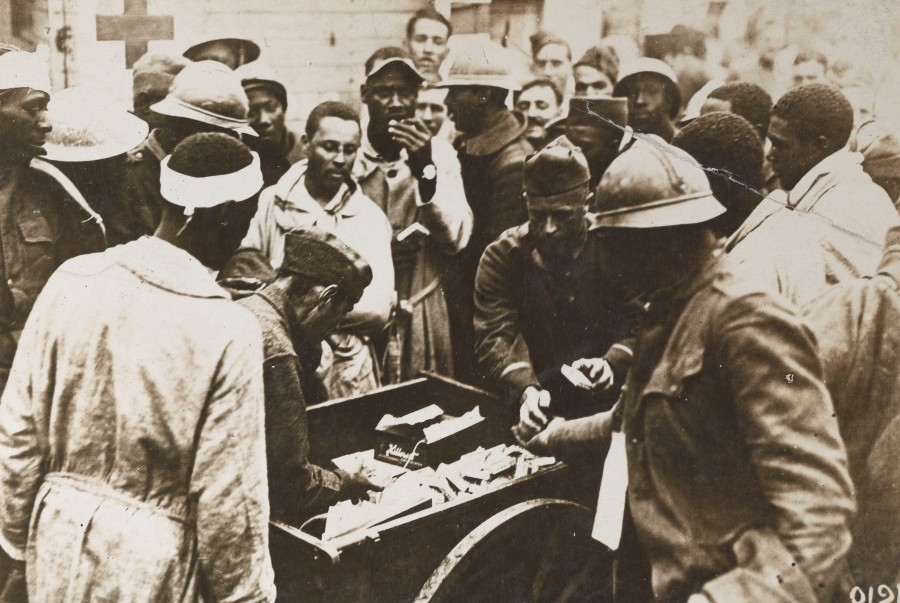 American Red Cross workers distribute chocolate, cigarettes, and other items to wounded soldiers of the 93rd Division at the American Red Cross Hospital No. 5 at Auteuil, France.  Local Identifier, 165-WW-127-81.