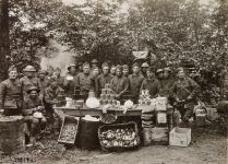 Original Caption: Mess Sergeant A. C. Carlson of H.D.Q. Co. of the 305th Infantry, and some of his well fed men. Ration display in the foreground. Abri du Cruchet, Ardennes, France. October 4, 1918. Local Identifier: 111-SC-29859