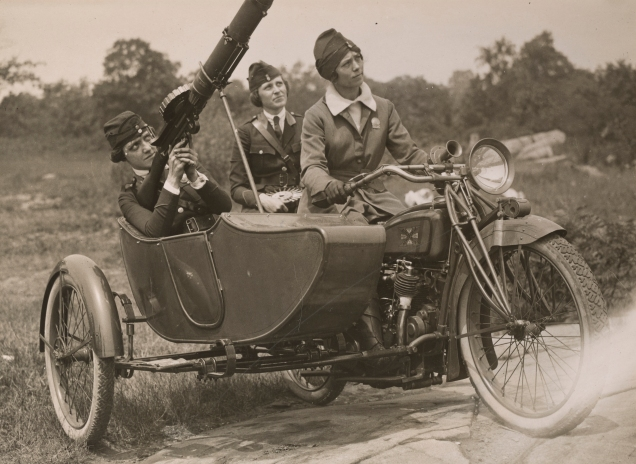 """""""Women's Machine Gun Squad Police Reserves, New York City - Praciticing with Lewis Machine gun, which is to be sent to the front....Capt. Elise Reniger manning the gun, Miss Helen Striffer on the rear seat, and Mrs. Ivan Farasoff driving."""" Date taken: August 1918 (Local ID: 165-WW-143B-23)"""