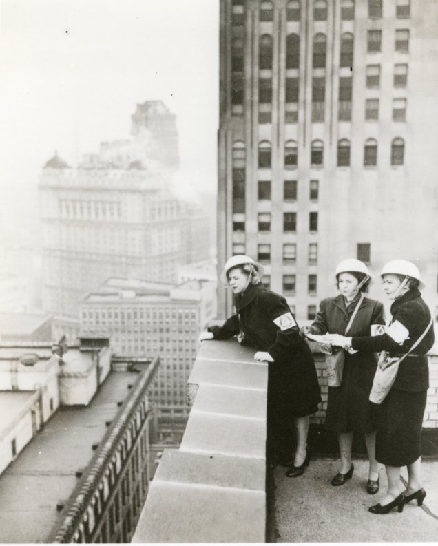 """""""From their observation posts on a downtown Detroit office building, these three women fire watchers study the roofs of surrounding buildings which are in their care. The women, members of the only OCD womens' fire watcher unit in the country, are required to serve four hour shifts during times of emergency."""" Date Taken: 1942 (Local ID: 171-OCD-109-C)"""