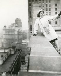 """""""Leaning against a parapet of a downtown Detroit office building, Miss Elizabeth Lakeman, a member of the nation's only OCD women fire watcher unit, signals a companion after she has discovered a simulated bomb burning on the roof of a nearby building."""" Date Taken: 1942 (Local ID: 171-OCD-111-C)"""