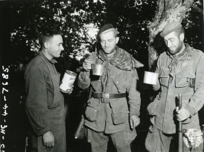 "111-SC-324432 ""Pvt. John C Rodrigues, Pawtuckett, R.I., gives two weary paratroopers their first taste of GI food in 37 days. They were captured by the Germans the latter part of D-Day, escaped after several days imprisonment during a night march , living off raw potatoes most of the time. They contacted US forces on July 15th 1944. Left to right: Sgt. Robert D. Henderson, Seattle, WA, and Sgt. Havrill W. Lazenby, Nashville, TN. 505th Parachute Regiment, 82nd Airborne Division."" July 17th 1944."