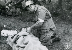 "111-SC-190228-S ""An American Medical Officer , who went to France with an Airborne Division, (82nd), lights a cigarette for a wounded American whose landing was less successful than that of the officer. St. Mere Eglise, France. 82nd Airborne Div."" June 12th 1944."
