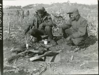 """(Local Identifier: 111-SC-354712) Johnnie Washington (NYC, NY) and Wilbert H. Davis, both of the 25th Infantry Regiment, decide to do a little """"Home Cooking"""" at Pong Dong, Korea and barbecue a pig to supplement their regular rations."""