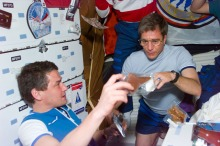"""(Local Identifier: 255-STS-S79E5242) """"Mir 22 commander Valerie Korzun makes a selection from various food packets with the help of astronaut John Blaha . They and the other members of the STS-79 and Mir 22 crews are sharing a barbecue dinner on the Atlantis's middeck"""""""