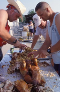 """(Local Identifier: 330-CFD-DF-ST-96-00276) """"CM3 Dan Ward, left, CM2 Russell Couhran, right, both mechanics; and, equipment operator EO1 Steven Moose Musnicky, Seabees from Port Hueneme, Calif, take charge of the pig roast. The pigs were cooked the night before and now the men are busily carving the carcass for the Independence Day cookout at Camp Pleso."""""""