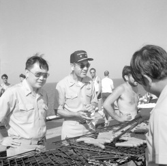 """(Local Identifier: 330-CFD-DN-SN-85-11086) """"Rear Admiral (RADM) Lawrence Chambers, commander, Carrier Group Three (center), and his chief of staff, Captain (CAPT) Ming Chang participate in the cookout during Stand Down Day aboard the aircraft carrier USS CORAL SEA (CV 43)."""""""