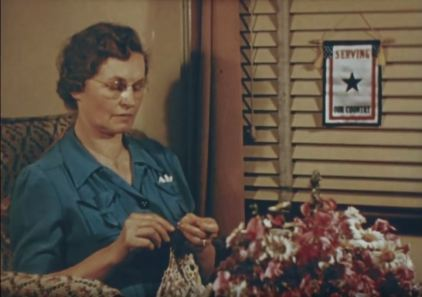 A mother with a blue star banner that indicates she has a child serving overseas. This scene is part of the story that Ford added to the documentary to make it more relatable for Americans on the home front.