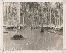 "127-GR-14-88-74085: Knee Deep in Guadalcanal. Four Marines wade up the main street of their camp area on Guadalcanal, while a fifth (first tent on the left) bails out his foxhole. There were times it was easier to row than walk and this was one of them. Guadalcanal has two seasons, the rainy, between November and May, and the wet. The only difference is that during the wet season there are no floods. Or as the natives put it when the rainy season comes: ""White men leave the island, and natives die."" American Marines, soldiers and sailors couldn't leave the island and when the rainy season reached its peak recently they were amazed at the vast quantities of water that poured constantly from the clouds. As much as eight inches of rain fell in 24 hours and rivers rose as high as seven feet above normal in two hours. Practically everything was under water and most forms of transportation was by boat."