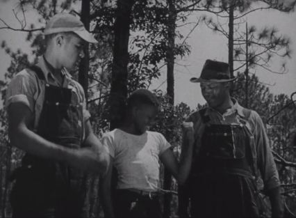 James Hunter shows off his new muscles after a day of work in the forest with his father and brother. (Still from Men of the Forest)
